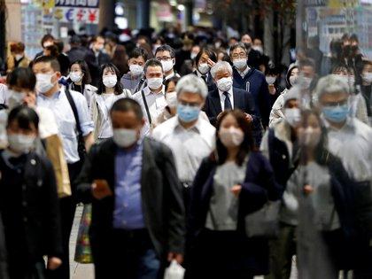 FILE PHOTO: People wearing protective face masks walk on the street, amid the coronavirus disease (COVID-19) outbreak, in Tokyo, Japan November 19, 2020. REUTERS/Issei Kato/File Photo
