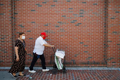 Teresa Guerra and Joaquin Luciano take two free bags of potatoes distributed by the Chelsea Collaborative amid the coronavirus disease (COVID-19) outbreak, in Chelsea, Massachusetts, U.S., July 21, 2020.   REUTERS/Brian Snyder
