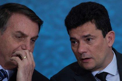 El presidente brasileño, Jair Bolsonaro (i), hablando con el ex ministro de Justicia y Seguridad, Sergio Moro. EFE/Archivo