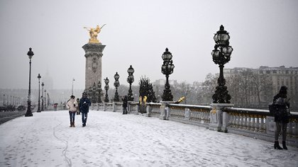 Parisians walk across the Iena bridge on January 16, 2021 during the snowfall in Paris (Photo by MARTIN BUREAU / AFP)