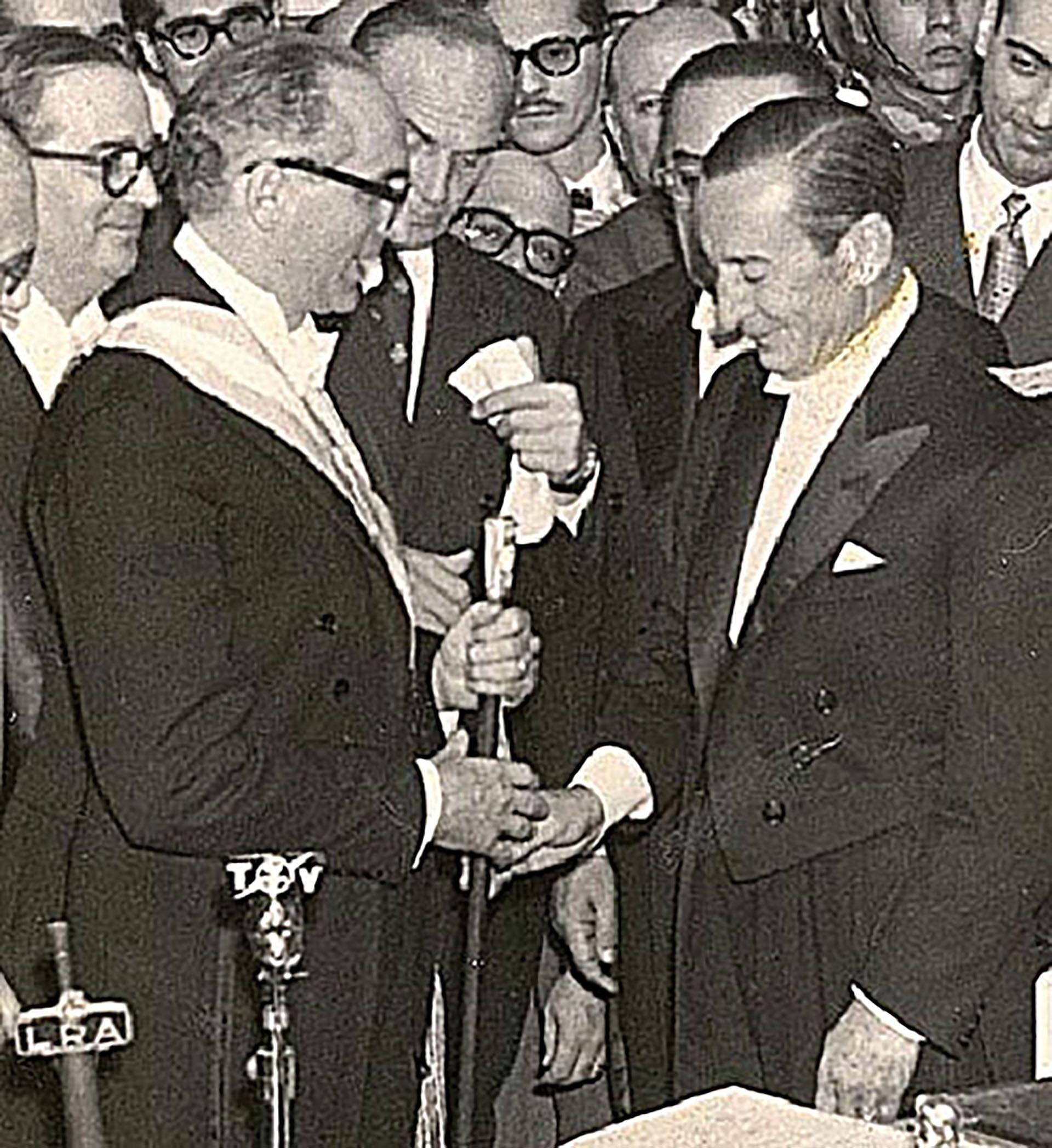 """Mayo de 1958: Arturo Frondizi recibe el bastón presidencial de manos de Eugenio Aramburu, uno de los líderes de la """"Revolución Libertadora"""" que había derrocado a Perón en 1955. En su primer año en el gobierno, Frondizi alcanzaría la """"brecha cambiaria"""" más alta de la historia argentina"""