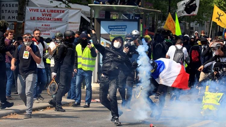El gas lacrimógeno flota alrededor de los manifestantes enmascarados durante los enfrentamientos con la policía antidisturbios francesa durante una manifestación como parte del tradicional día del trabajo en París (Reuters)