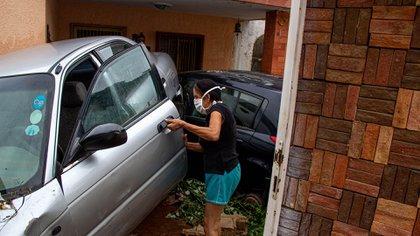 Una mujer revisa un vehículo que fue arrastrado y dañado por la lluvia en Maracaibo (EFE/ Henry Chirinos)