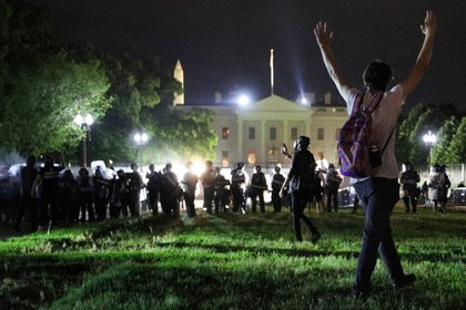 Un manifestante levanta las manos al entrar la policía en el Parque Lafayette, mientras los oficiales mantienen a los manifestantes alejados de la Casa Blanca durante una protesta en Washington, EEUU, el 30 de mayo, 2020. REUTERS/Tom Brenner