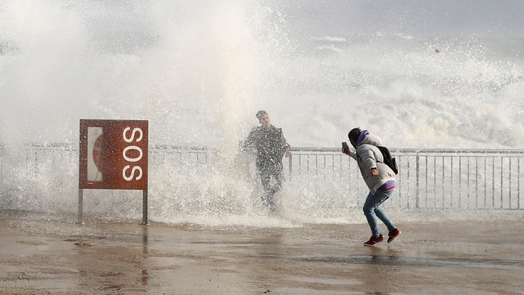 Turistas toman fotografías de las olas durante la tormenta