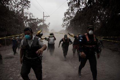 Un grupo de policías de Guatemala ayudan a evacuar a los residentes de la aldea El Porvenir (EFE/JOSE MISA)