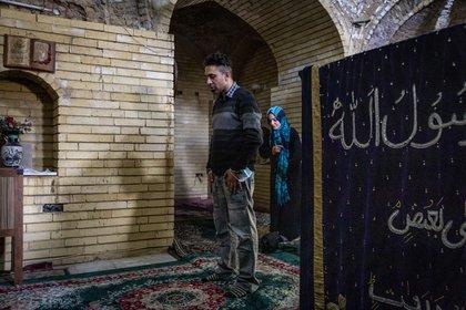 Salih Ahmed Salih y su esposa, Arwa Sameer, oraron junto a la tumba del profeta Joshua con la esperanza de curar el severo dolor de espalda de Sameer, en Bagdad el 29 de enero de 2021.. (Ivor Prickett/The New York Times)