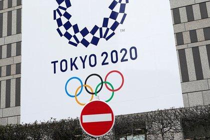 Una señal de prohibido el paso se sitúa frente a un cartel anunciador de los Juegos Olímpicos de Tokio 2020 en un edificio oficial en Tokio, Japón. EFE/ Franck Robichon/Archivo