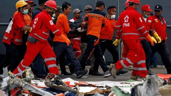 Rescatistas trasladan un cuerpo encontrado en el agua tras la tragedia (Reuters)