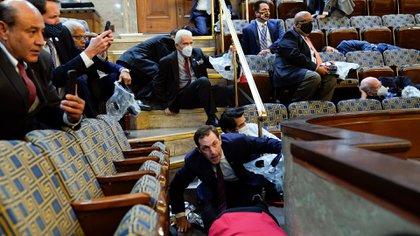 Un grupo de funcionarios del Congreso se refugia en la galería de la Cámara de Representantes mientras los manifestantes tratan de entrar al recinto (Foto AP/Andrew Harnik)