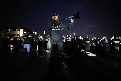 Una persona utiliza un megáfono en Brooklyn Center mientras los activistas se enfrentan a policías estatales, miembros de la Guardia Nacional y otros agentes de la ley después de una marcha por Daunte Wright, de 20 años, que fue asesinado a tiros por la ex agente de policía Kim Potter (REUTERS/Nick Pfosi)