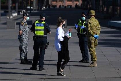 Una mujer con máscara facial camina frente a oficiales de policía de Victoria y personal militar en las afueras del Museo de Melbourne, Australia. AAP Image/James Ross via REUTERS