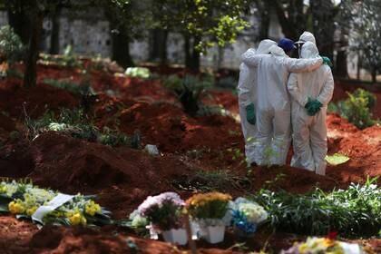 Sepultureros con trajes protectores se reúnen en el cementerio de Vila Formosa, el cementerio más grande de Brasil, durante el brote de la enfermedad por coronavirus (COVID-19), en San Pablo, Brasil [2 de abril de 2020] (Reuters/ Amanda Perobelli)