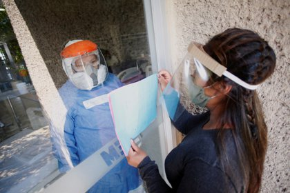 Una mujer visita a su familiar enfermo de COVID-19 desde una ventana de un cuarto de hospital para evitar contagiarse   (Foto: Reuters/Gustavo Graf)