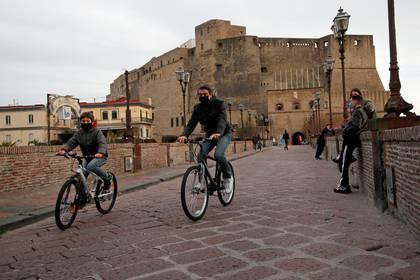 Una familia circula en bicicleta por Nápoles, todos con mascarillas (Reuters)