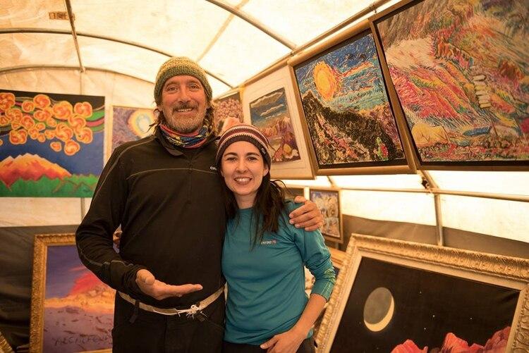 Miguel Doura en su galería de arte en el Aconcagua, junto a una visitante.