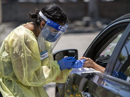 03/06/2020 03 June 2020, US, Los Angeles: A medical worker wears protective equipment takes a sample from a person at a drive-through COVID-19 testing clinic at the Weingart YMCA Wellness and Aquatic Center. Photo: Hans Gutknecht/Orange County Register via ZUMA/dpa