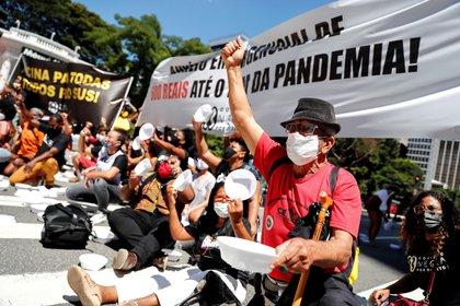 Integrantes de la Coalición Negra Por Derechos, alianza compuesta por más de 200 movimientos sociales y afro, participan hoy en una manifestación con platos vacíos frente a la sede del Banco Central de Brasil, en la avenida Paulista, en Sao Paulo (Brasil). EFE/ Sebastiao Moreira