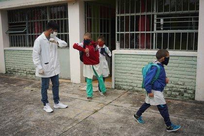 El maestro saluda con el codo a sus alumnos (REUTERS/Mariana Greif)