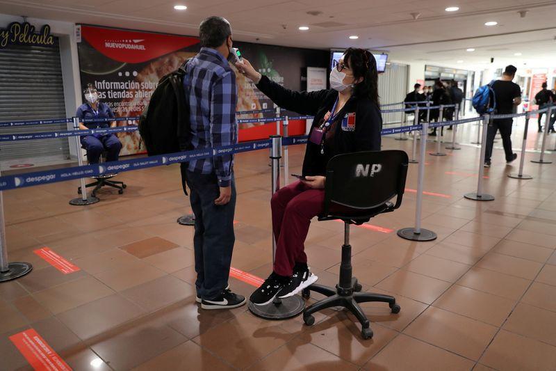 FOTO DE ARCHIVO: Una trabajadora comprueba la temperatura de un pasajero mientras el país abre su frontera aérea en medio de la propagación de la enfermedad del coronavirus (COVID-19), en el Aeropuerto Internacional de Santiago, Chile. 23 de noviembre de 2020. REUTERS/Iván Alvarado