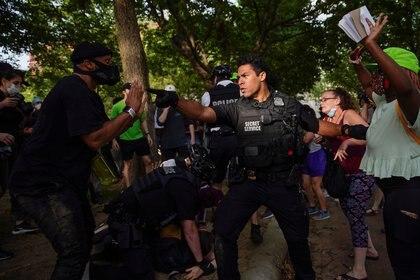 """Mezclado entre la multitud, un oficial con la leyenda """"Servicio secreto"""" en su uniforme señala a un manifestante durante una marcha hacia la Casa Blanca para protestar por la muerte de George Floyd (REUTERS/Eric Thayer)"""