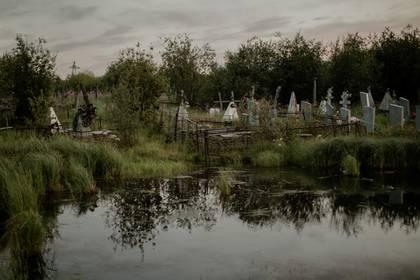 El agua inundó el cementerio en Srednekolimsk y afectó las tumbas. (Emile Ducke/The New York Times)