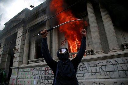 Un hombre protesta en frente del Congreso de Guatemala en llamas ocasionado por manifestantes que protestan contra del Gobierno del presidente, Alejandro Giammattei hoy en Ciudad de G. EFE/Esteban Biba
