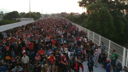 Cientos de migrantes centroamericanos que en caravana huyen de la pobreza y violencia, la mayoría hondureños, buscaban el lunes en un puente fronterizo entre Guatemala y México que las autoridades mexicanas les permitan el ingreso en masa para continuar a Estados Unidos.