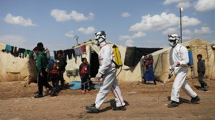 Miembros de la Defensa Civil de Siria desinfectan el campamento de desplazados internos de Bab al Nour para prevenir la propagación del coronavirus, en Azaz, Siria (Reuters/ Khalil Ashawi)