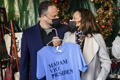"""FILE -- Vice President-elect Kamala Harris and her husband, Doug Emhoff, hold up a t-shirt that says """"Madam Vice President"""" while visiting small businesses at a holiday market on Small Business Saturday in Washington, on Nov. 28, 2020. What's it like to have Kamala Harris as 'Momala'? Her stepkids Cole and Ella Emhoff weigh in.  (Samuel Corum/The New York Times)"""