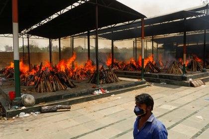 Un hombre pasa junto a las piras funerarias en llamas de los que murieron por la enfermedad del coronavirus (COVID-19), durante una cremación masiva, en un crematorio en Nueva Delhi (Reuters)