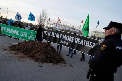 Activistas contra el cambio climático de Extinction Rebellion sostienen letreros luego de descargar un camión lleno de excremento de caballo frente al recinto en el que se realiza la Conferencia de Cambio Climático de Naciones Unidas COP25 en Madrid, España. 14 de diciembre, 2019. REUTERS/Nacho Doce