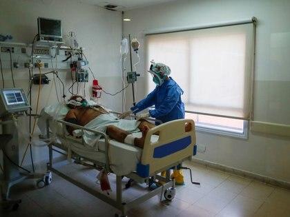 Un trabajador de la salud atiende a un paciente con COVID-19 en una unidad de cuidado intensivo del HospitalDr. Alberto Antranik Eurnekian, en Ezeiza, en las afueras de Buenos Aires, Argentina, Agosto 21, 2020. REUTERS/Agustin Marcarian