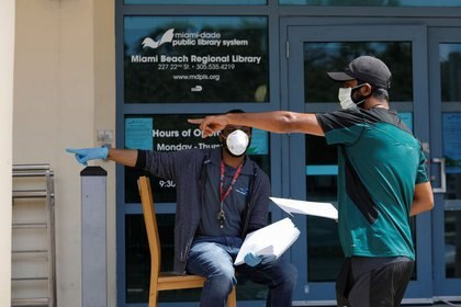 Un hombre conversa con un trabajador de una librería tras recibir un formulario de subsidios por desempleo en Miami Beach. April 8, 2020. REUTERS/Marco Bello