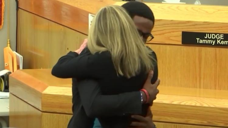 La mujer y el joven se abrazan.