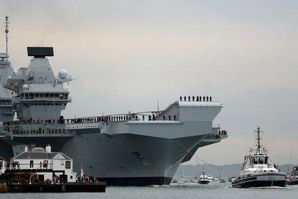 El portaaviones de la Royal Navy, HMS Queen Elizabeth, es remolcado por remolcadores cuando llega a la base naval de Portsmouth, Gran Bretaña, el 16 de agosto de 2017. (REUTERS / Peter Nicholls / Foto de archivo)