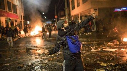 Un hombre lanza piedras en medio de los incidentes (AP Photo/Ivan Valencia)