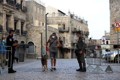 El personal de seguridad israelí se para en un punto de control después de que Israel ingresó a un segundo bloqueo en todo el país en medio de un resurgimiento de nuevos casos de enfermedad por coronavirus (COVID-19), lo que obligó a los residentes a permanecer principalmente en casa durante la temporada alta de vacaciones judías, junto a la Puerta de Jaffa a Jerusalén. REUTERS/Ronen Zvulun/File Photo