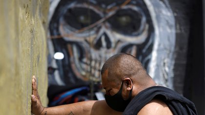 A man wearing protective face mask prays during a mass on the first day of the reopening of the temple of the cult figure La Santa Muerte (The Saint of Death) after government restrictions were eased, amid the coronavirus disease (COVID-19) outbreak in Tultitlan, on the outskirts of Mexico City, Mexico July 26, 2020. REUTERS/Luis Cortes