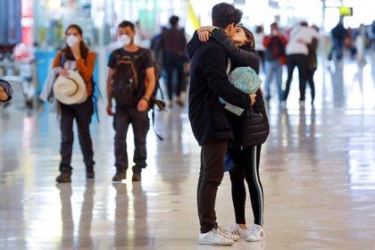 Una pareja se besa en el aeropuerto Madrid-Barajas Adolfo Suárez, junto a otros viajeros protegidos con mascarillas. EFE/Emilio Naranjo/Archivo