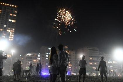 Una pareja contempla los fuegos artificiales conmemorativos del Año Nuevo en Copacabana, Brasil