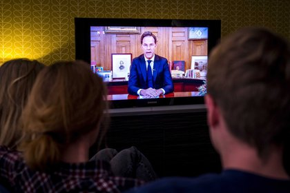 A family follows Dutch Prime Minister Mark Rutte's speech on television