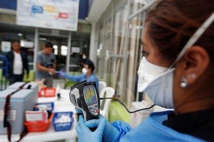 Personal del ministerio de salud verifica la temperatura de un turista en medio del brote de coronavirus, en el puente fronterizo de Rumichaca en Tulcan, Ecuador (REUTERS/Daniel Tapia)