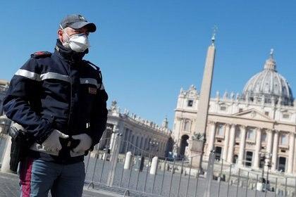 Un policía con mascarilla vigila la Plaza de San Pedro vacía en el Vaticano. (REUTERS/Guglielmo Mangiapane)