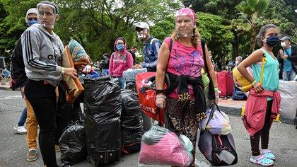 Unos 200 venezolanos, entre ellos 17 niños, que habían emigrado de su país en busca de un futuro mejor, emprendieron este martes el retorno desde la ciudad colombiana de Cali (Luis ROBAYO / AFP)