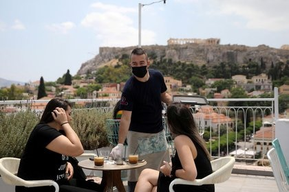 Foto de archivo ilustrativa de un mozo atendiendo al público en una cafetería de Atenas, con la Acrópolis de fondo.  May 25, 2020. REUTERS/Costas Baltas