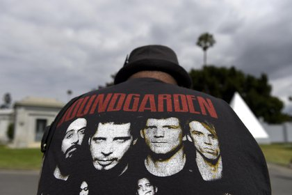 A fan wearing a Soundgarden T-shirt reacts following a funeral for Chris Cornell at the Hollywood Forever Cemetery on Friday, May 26, 2017, in Los Angeles. (Photo by Chris Pizzello/Invision/AP)