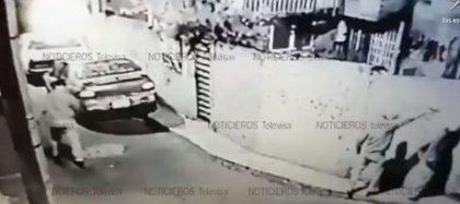 Una cámara de vigilancia capta el momento en que una persona con la cabeza cubierta es bajada de un taxi y colocada contra la pared. Segundos después, un hombre le apunta con un arma de fuego Fotografía: Captura de Pantalla / Noticieros Televisa