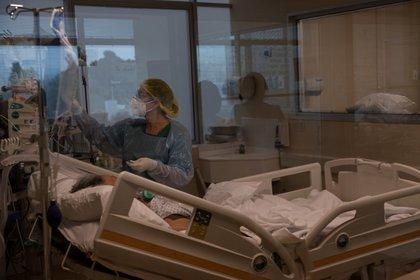 Una doctora del Hospital Militar revisa los signos vitales de un paciente con la COVID-19 que permanece entubado, en de Santiago (Chile). EFE/Alberto Valdés/Archivo