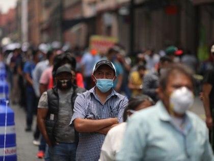 FOTO DE ARCHIVO: Varias personas con mascarillas hacen cola en una calle para acceder a un área comercian en Ciudad de México, México, el 6 de julio de 2020. REUTERS/Henry Romero